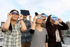 安全に日食メガネを使って観察する(アストロアーツ提供)